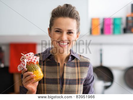 Portrait Of Happy Young Housewife Showing Jar With Pickled Veget