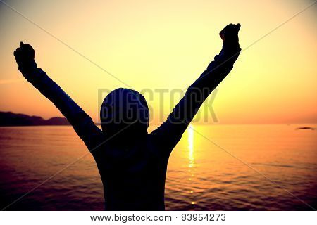 cheering woman open arms at sunrise seaside