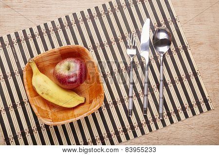 Bowl With Banana And Strawberry And Cutlery On The Table