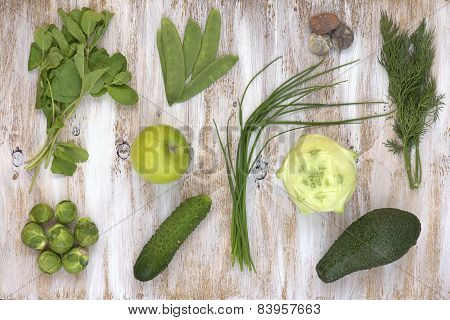 Set of green vegetables on white painted wooden background.