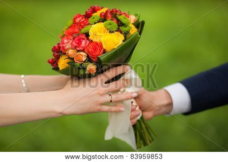 Close up of beautiful bouquet of fresh flowers. man and woman hands.