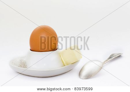 White Eggcup With Brown Egg, Spoon And Butter With Salt