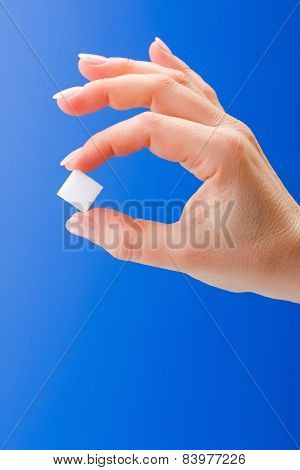 Woman's Hand Holding A White Sugar Cube