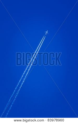 Airplane In The Sky With Plane Trails