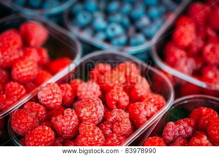 Baskets Full Of Raspberries And Blueberries On The Farmers Marke