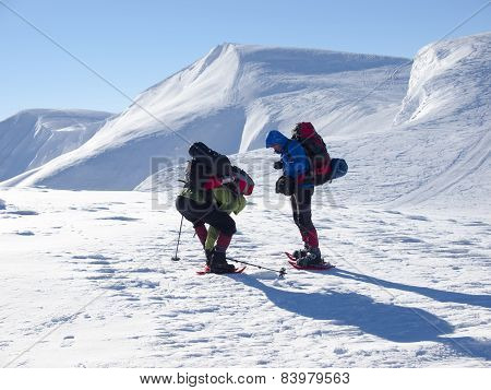 Men In Snowshoes Go In The Mountains.