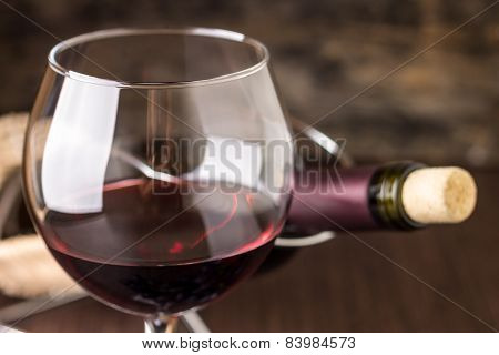 Red Wine In Wineglass Against Corked Bottle