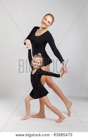 Mom and daughter are dancing. Woman teaching kid