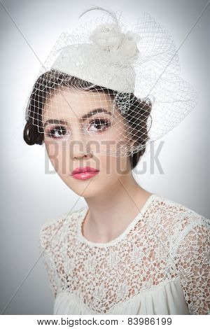 Hairstyle and make up - beautiful young girl art portrait. Cute brunette with white cap and veil