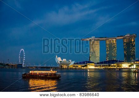Riverboat cruises the harbor in Singapore at sunset