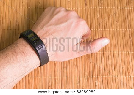 Hand on wood table wearing a fitness tracking armband
