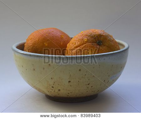 Oranges in Ceramic Bowl on white