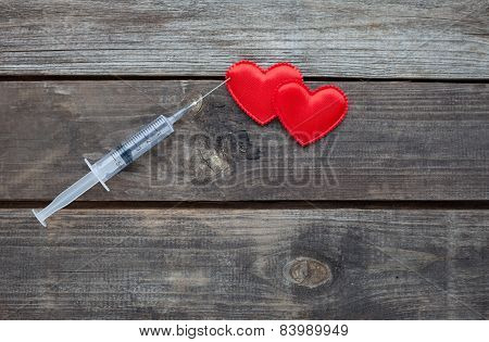 Red Heart And Syringe On Wooden Background. Drug Addiction Concept