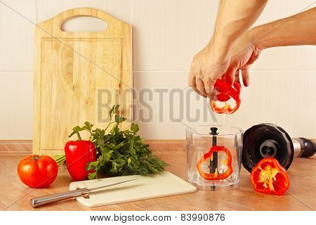 Hands chefs put chopped red pepper in blender