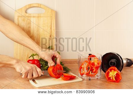 Hands cook cut tomato on kitchen table