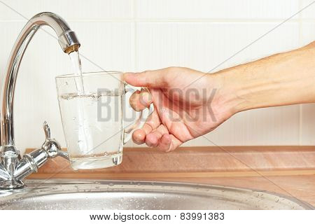 Hands pour fresh water into the glass under the tap in kitchen