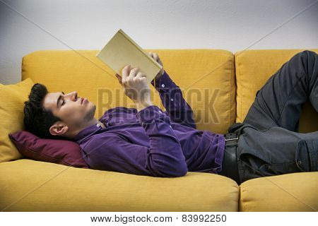 Handsome black haired young man reading book at home