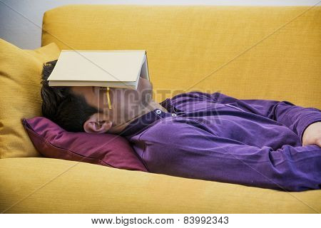Over-worked, tired young man at home sleeping under book
