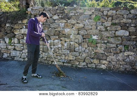 Young man outdoor sweeping foliage with broom