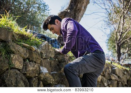 Handsome young man climbing stone wall