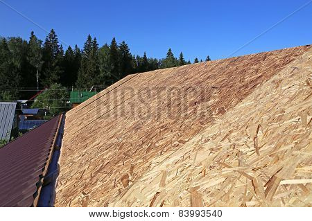 Covering The Roof Of A Wooden House A Metal Tile