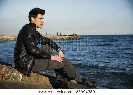 Handsome fashionable young man sitting at sea or ocean shore