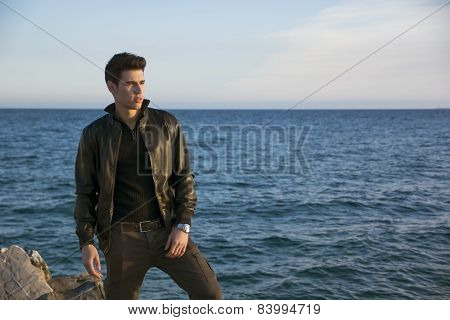 Handsome fashionable young man at the seaside along the shore