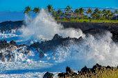 image of shoreline  - Big waves crashing onto rocky shoreline on a sunny day - JPG