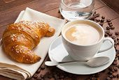 stock photo of croissant  - Cappuccino with croissant and glass of water in the tray of brown wood - JPG