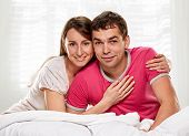 stock photo of laying-in-bed  - Happy smiling couple laying laughing in bed - JPG
