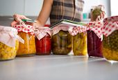 stock photo of pickled vegetables  - Closeup on jars of pickled vegetables and housewife writing in notepad - JPG