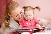 stock photo of nurture  - pretty mom reading a book to baby daughter at home - JPG