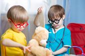 stock photo of home remedy  - kids boys playing doctor with plush toy at home - JPG