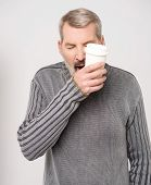 pic of yawn  - Sleepy man is yawning with a cup of coffee - JPG