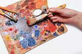 stock photo of paint palette  - The artist paints a picture of a paint brush in his hand with a palette closeup - JPG