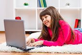 stock photo of pre-adolescent girl  - Cute little girl is using laptop at her home - JPG