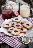 foto of linzer  - Homemade Linzer cutout jam filled cookies on table - JPG