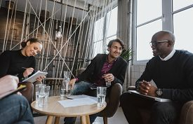 pic of coworkers  - Relaxed young executives having a meeting indoors - JPG