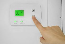 picture of temperature  - A person adjusting the AC thermostat temperature - JPG