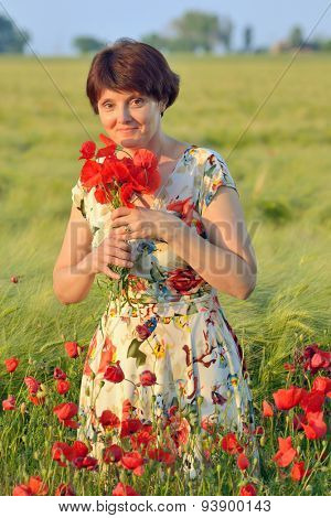 woman  in field of poppies in summer sunset