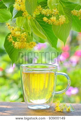 cup with linden tea and flowers on wooden table in garden