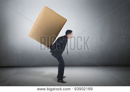 Asian Business Man Carrying Brown Package On His Back