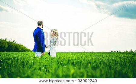 Wedding Couple In The Field With Green Grass