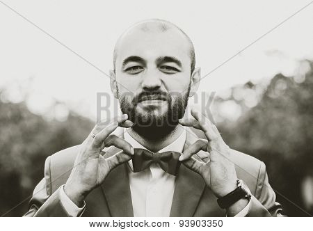 Man With Beard Holding His Bow Tie By Fingers, Grain Effect