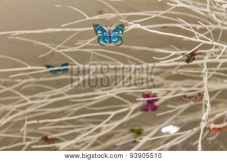 interior decoration with painted tree and colorful artificial butterflies on grey background