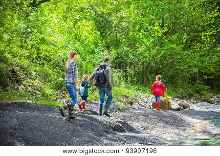 Happy Young Family With Two Little Daughters Near The Mountain River