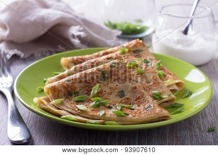 Pancakes with green onions and sour cream