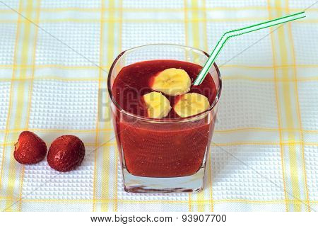 Strawberry smoothie in the glass with banana slices on the top
