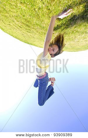 Young girl doing cartwheel across green grass on top of the world