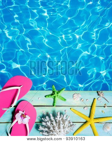 flip-flop, starfish, seashells and coral on wooden plank and pool - summer background
